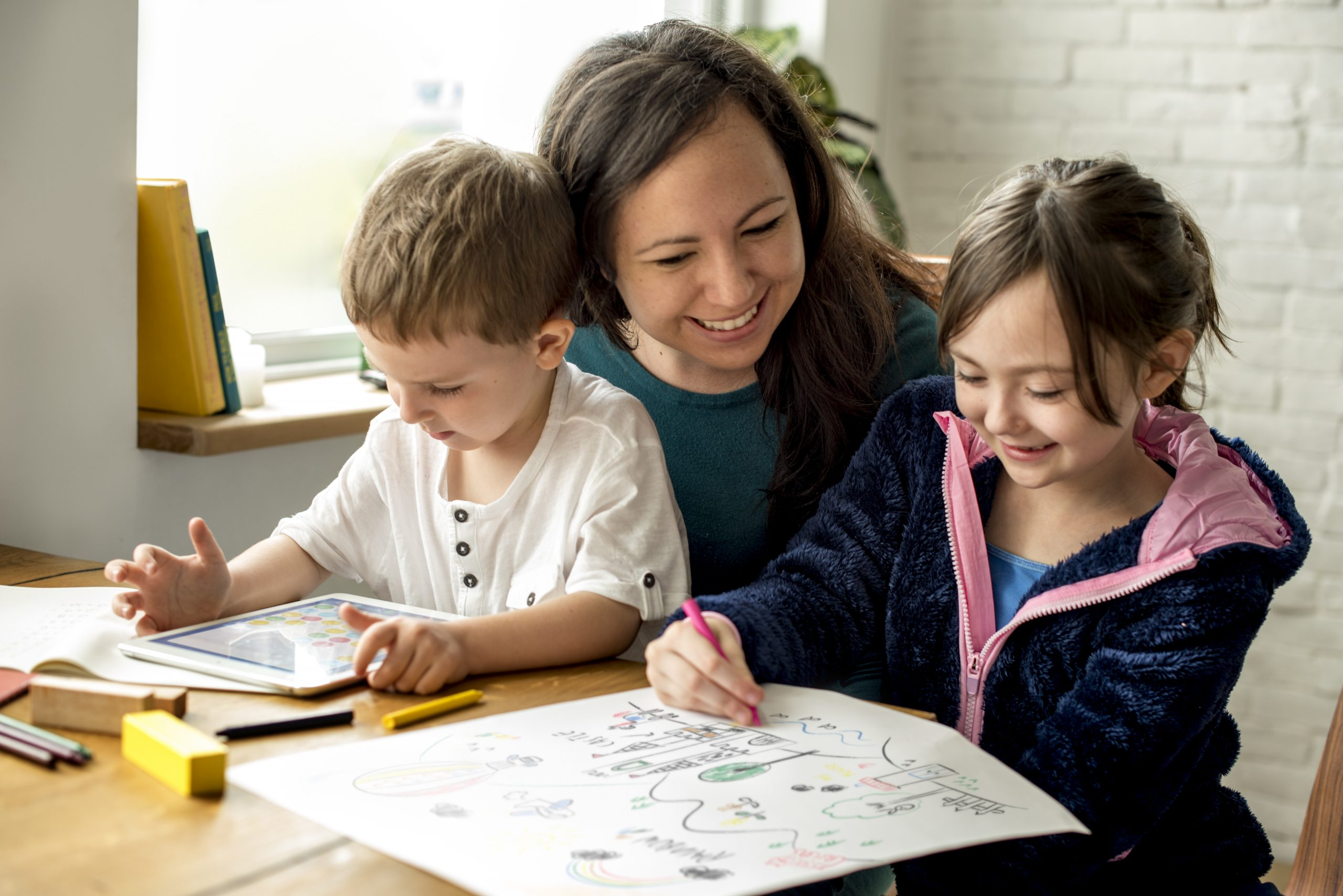Mum sits at table homeschooling two young children